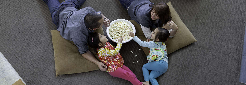 Family eating popcorn on carpet.